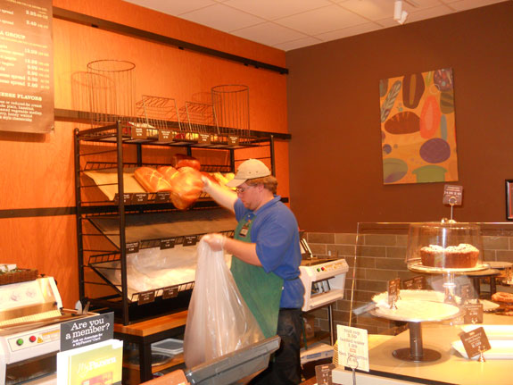 Panera Bread Employee bagging up bakery items for Helping Neighbors